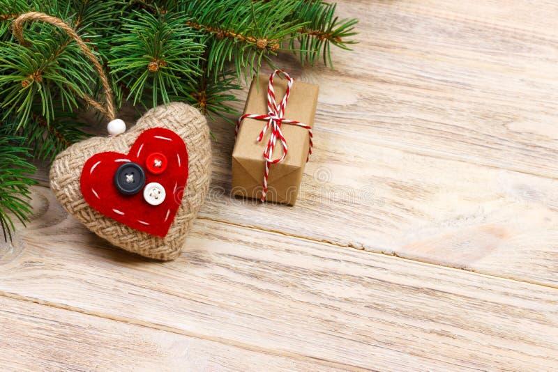 与红色礼物盒的圣诞树分支和在木桌上的红色心脏 与拷贝空间的顶视图 免版税图库摄影