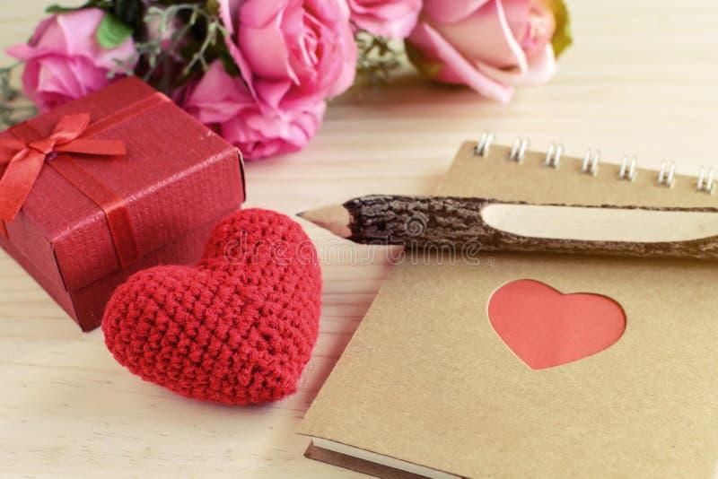 与红色礼物盒的空白的笔记薄和红色心脏塑造 免版税库存图片