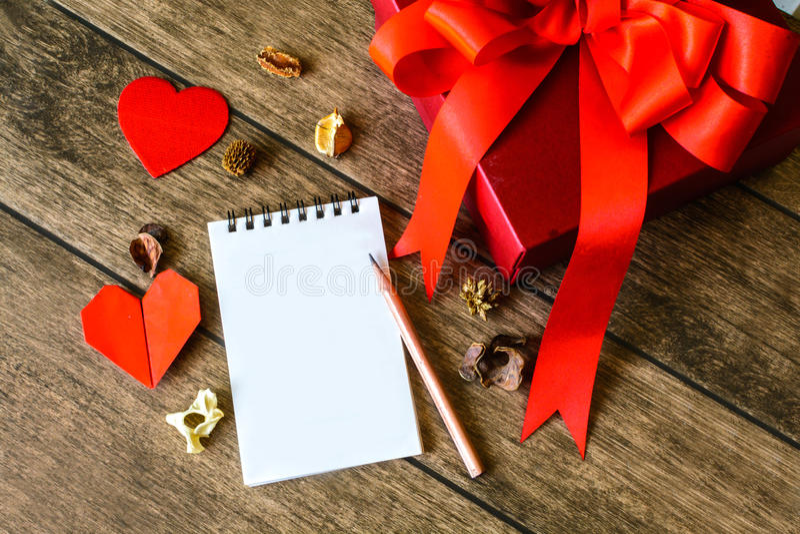 与红色礼物盒的空白的笔记薄 库存图片