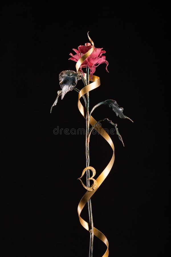 与红色绽放的玫瑰和一卷绿色茎和金磁带和心脏由金属制成 免版税图库摄影