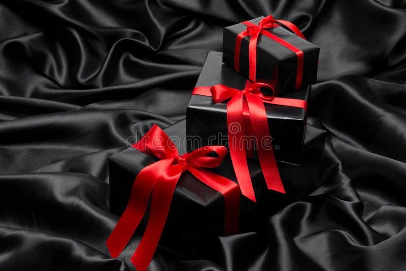 与红色缎丝带和弓的黑礼物boxe 免版税库存图片