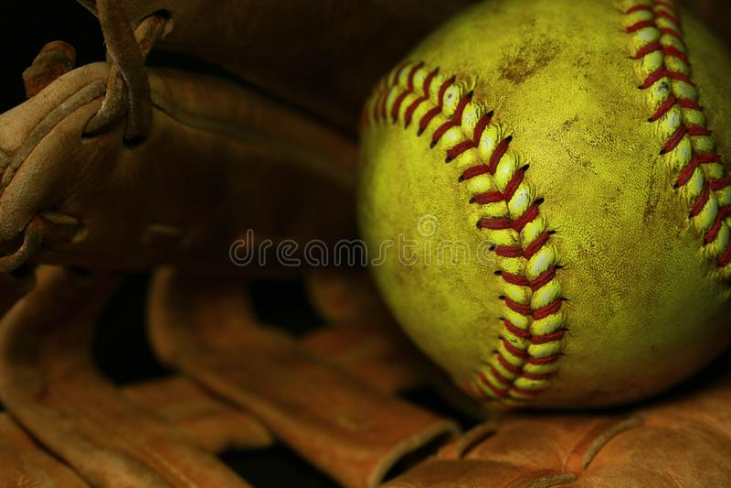 与红色缝的黄色垒球特写镜头在一个棕色皮手套 库存照片