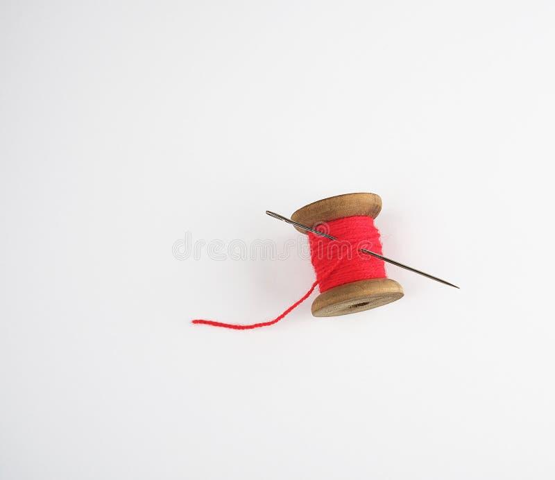 与红色羊毛螺纹和一根大针的木卷轴 库存图片