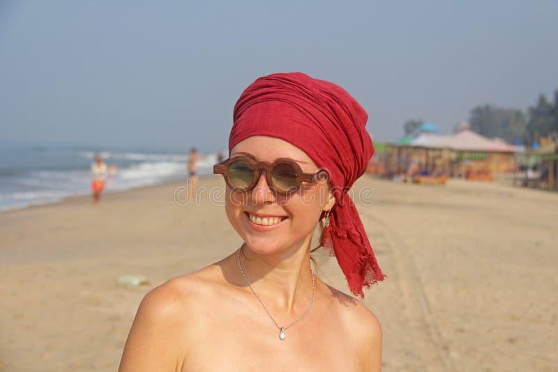与红色臂章的美丽的女孩畸形人在她的头,在后面 免版税图库摄影