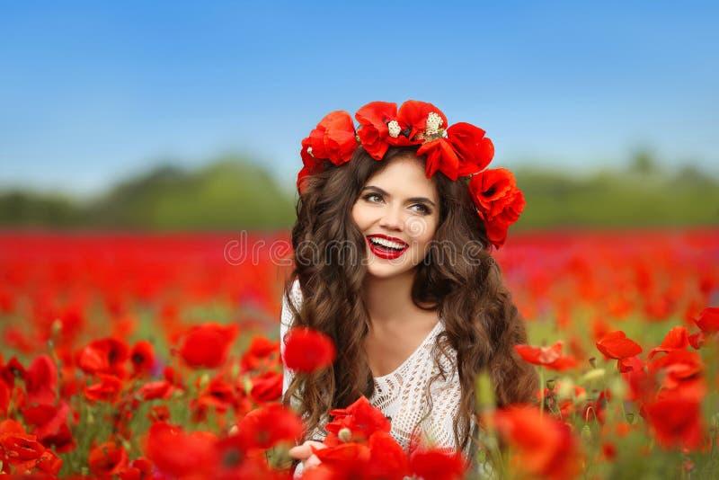 与红色花的美丽的愉快的微笑的青少年的女孩画象在h 免版税图库摄影