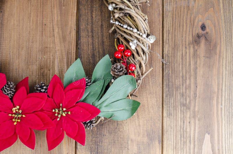 与红色花的自创圣诞节花圈在木背景,文本的地方 免版税库存照片