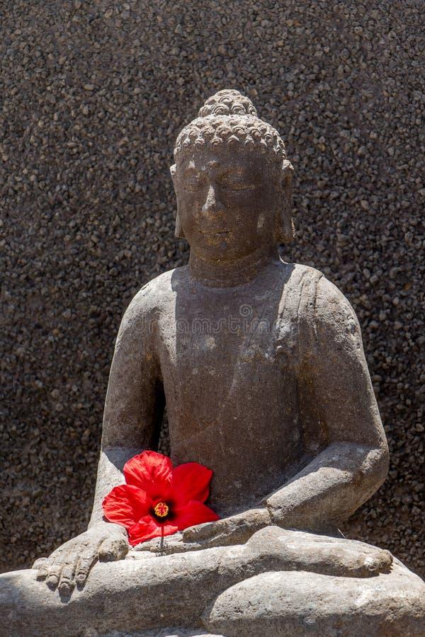 与红色花的Budha 免版税图库摄影
