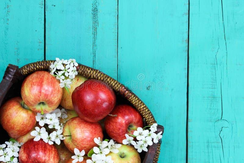 与红色苹果和白色春天的篮子在木桌上开花 库存照片