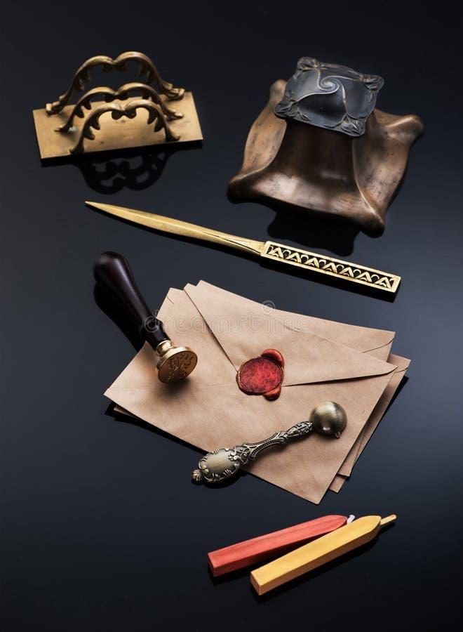 与红色蜡封印和葡萄酒文字集合的老信封:古铜色墨水池、封印、开信刀和匙子蜡的 免版税库存照片