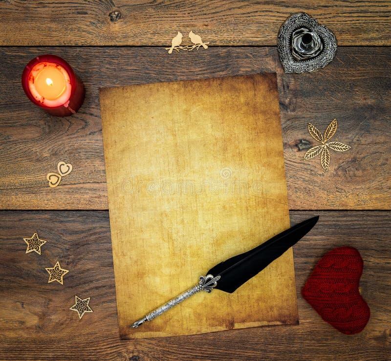 与红色蜡烛、红色拥抱牡鹿、木装饰、墨水和纤管的空白的葡萄酒卡片在葡萄酒橡木,在古色古香的橡木的情书 库存图片