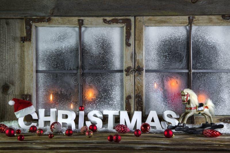 与红色蜡烛、马和问候tex的土气圣诞节窗口 库存照片