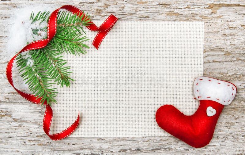 与红色袜子的圣诞卡,丝带和冷杉分支 免版税库存图片