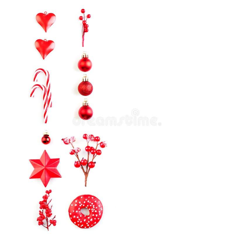 与红色装饰的圣诞节构成 在白色背景隔绝的圣诞节红色装饰、中看不中用的物品和糖果 Flatlay顶视图 库存照片