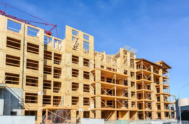 与红色起重机的住宅公寓在它上在蓝天背景 免版税库存照片