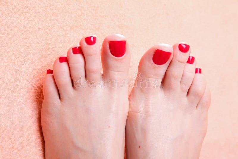 与红色趾甲的妇女脚在毛巾 免版税库存图片