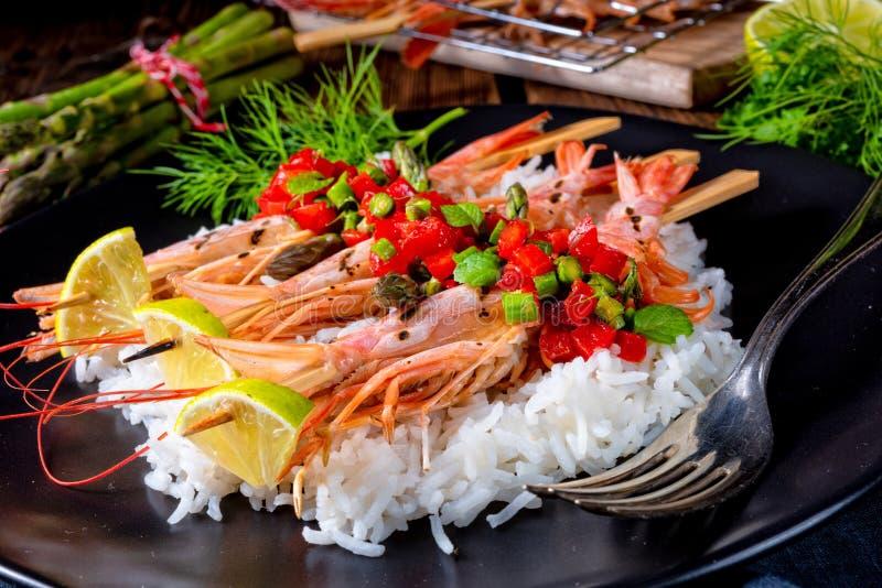 与红色辣调味汁和绿色芦笋的烤红色阿根廷虾 免版税库存照片