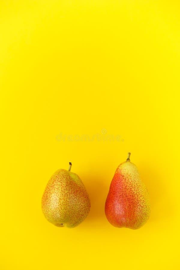 与红色边的两个开胃成熟梨在黄色背景 库存图片
