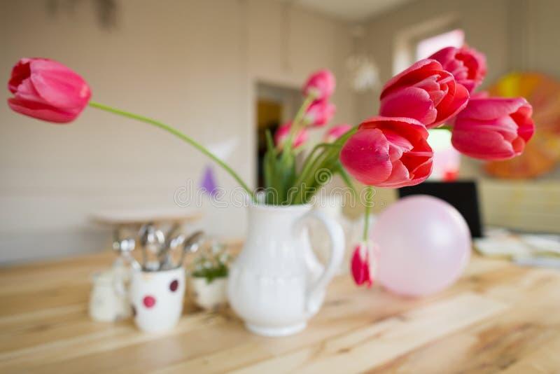 与红色郁金香的美好的桌设置,忘记在木桌上的我没有和杯子 免版税库存照片