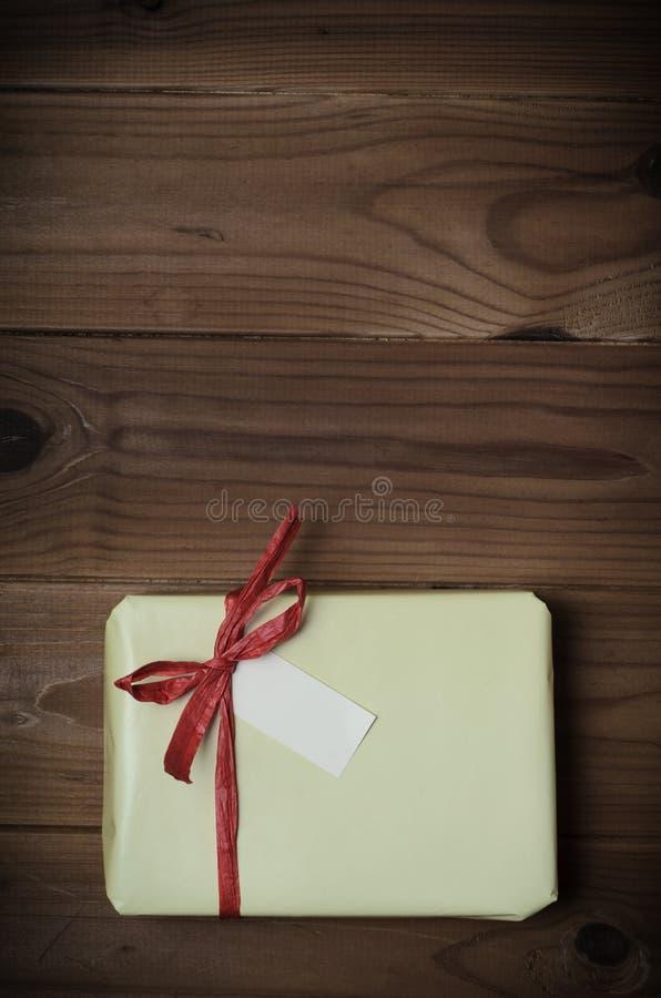 与红色酒椰弓的被包裹的礼物包裹在木铺板- Retr 库存照片