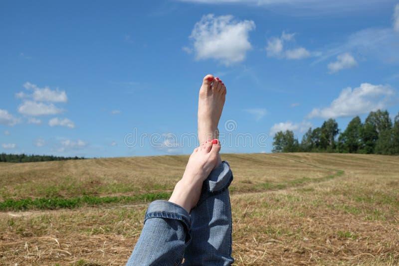 与红色钉子的女性赤脚反对夏天环境美化 库存照片