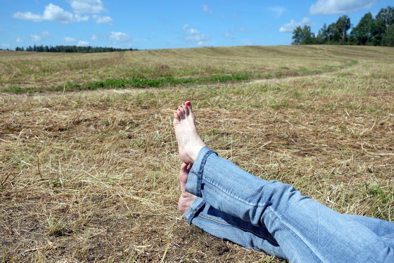 与红色钉子的女性赤脚反对夏天环境美化 免版税库存照片