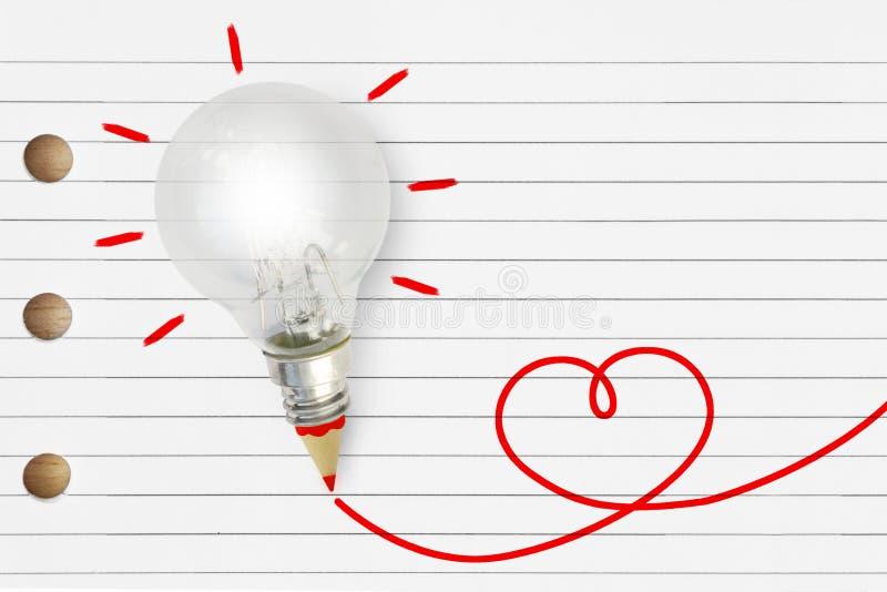 与红色铅笔和心脏剪影的电灯泡在镶边笔记本 免版税图库摄影