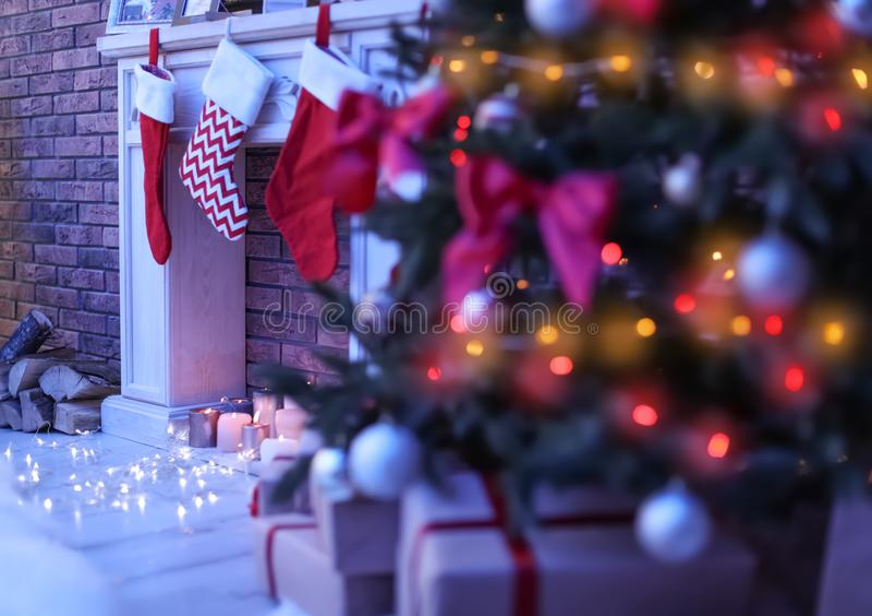 与红色长袜圣诞树的装饰壁炉在暗室 免版税库存照片