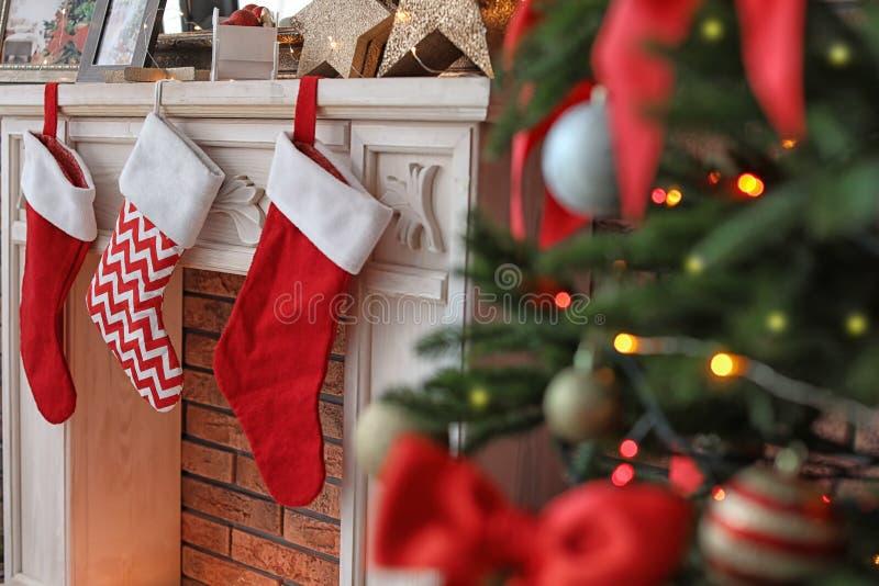 与红色长袜的装饰壁炉临近树户内 免版税库存照片