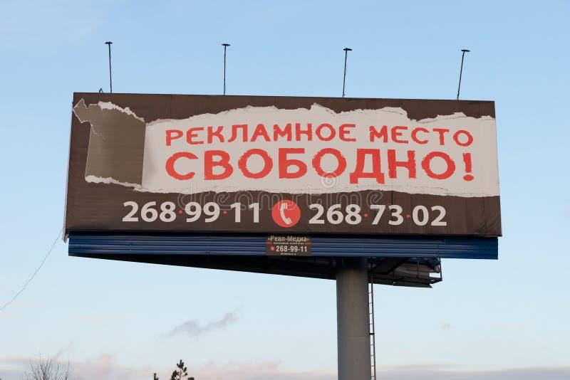 与红色题字的路旁广告牌用俄语-广告时间自由地,反对天空蔚蓝 图库摄影