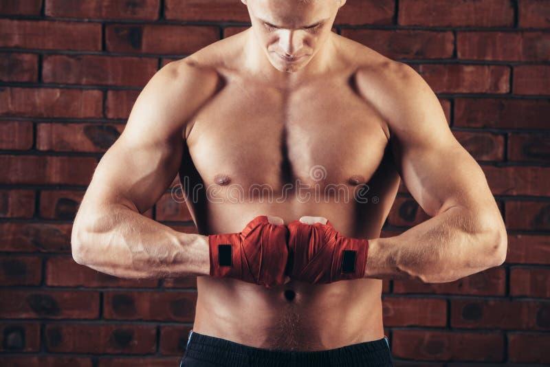 与红色绷带的肌肉战斗机以砖墙为背景 免版税库存图片