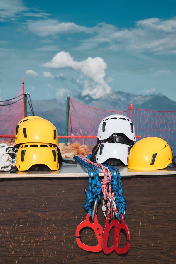与红色carabines的黄色和白色盔甲在山和多云天空背景 上升的安全保护系统设备 免版税库存照片
