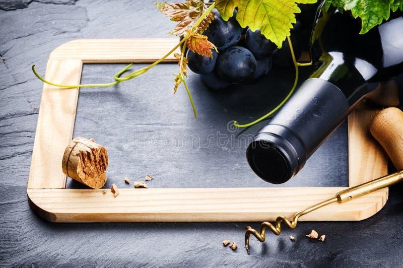 与红葡萄酒瓶和新鲜的葡萄的框架 免版税库存照片