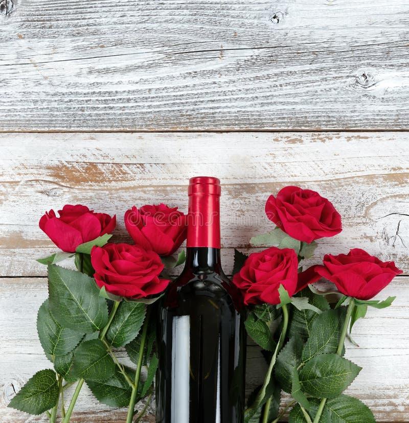 与红酒和玫瑰的情人节庆祝在白色土气木背景底部  图库摄影