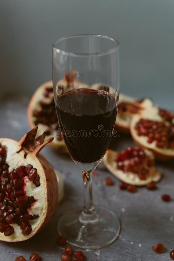 与红酒立场的一个酒杯在手榴弹旁边的灰色难看的东西背景 果子和石榴酒 免版税库存照片