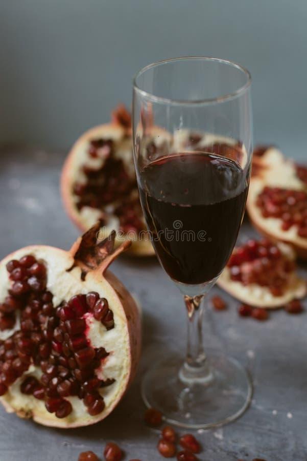 与红酒立场的一个酒杯在手榴弹旁边的灰色难看的东西背景 果子和石榴酒 库存图片