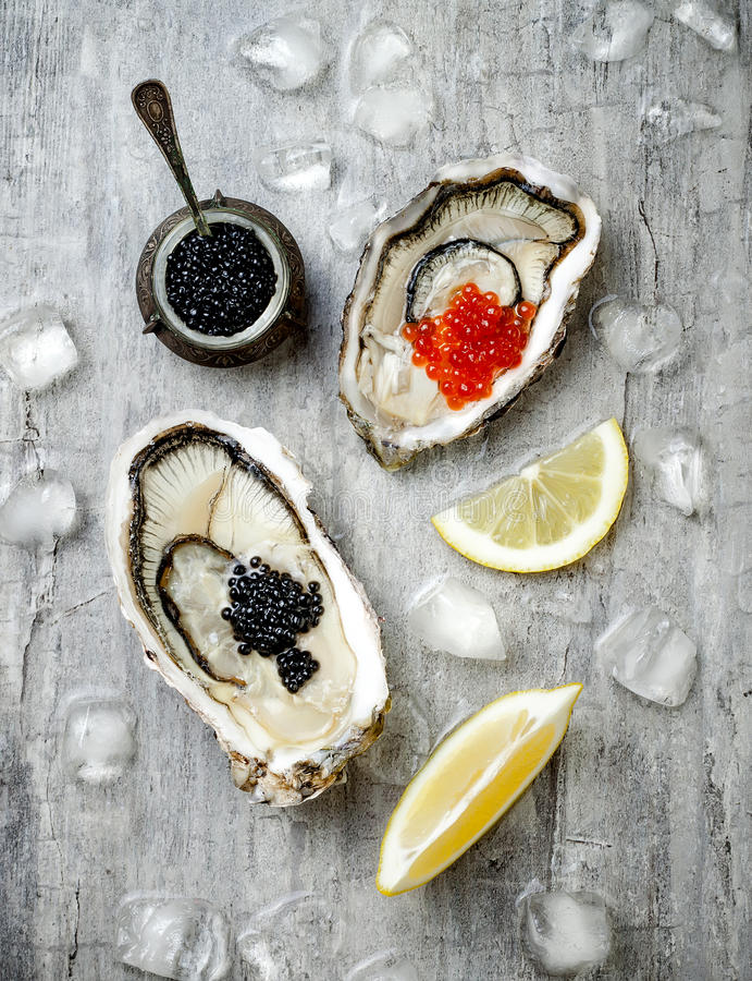 与红鲑鱼的被打开的牡蛎和黑鲟鱼鱼子酱和柠檬在冰在灰色具体背景 顶视图,平的位置 免版税库存图片