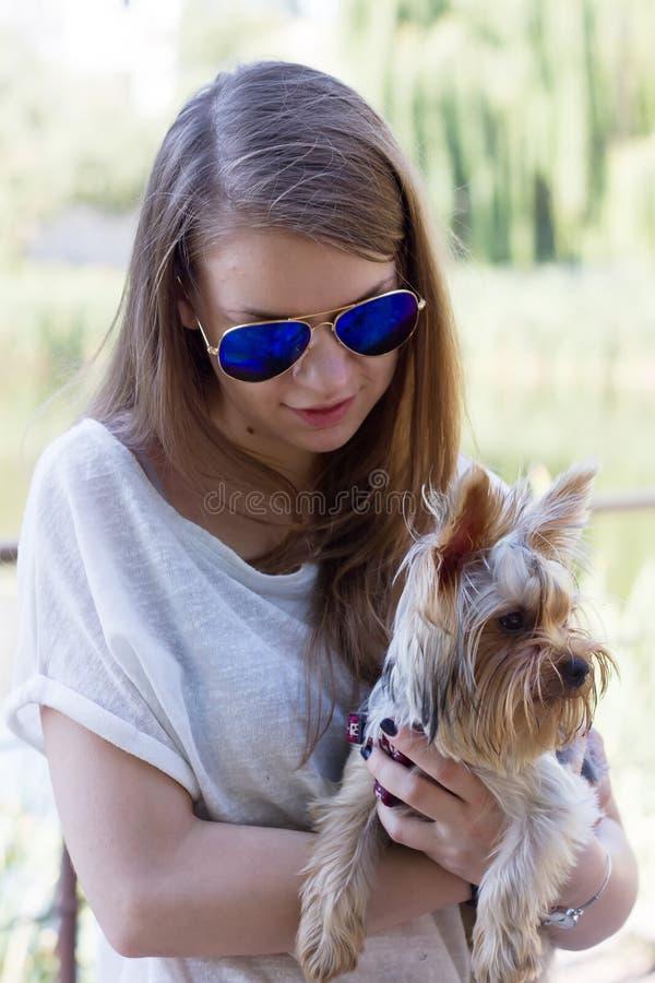 与约克夏狗狗的愉快的女孩所有者 免版税库存图片