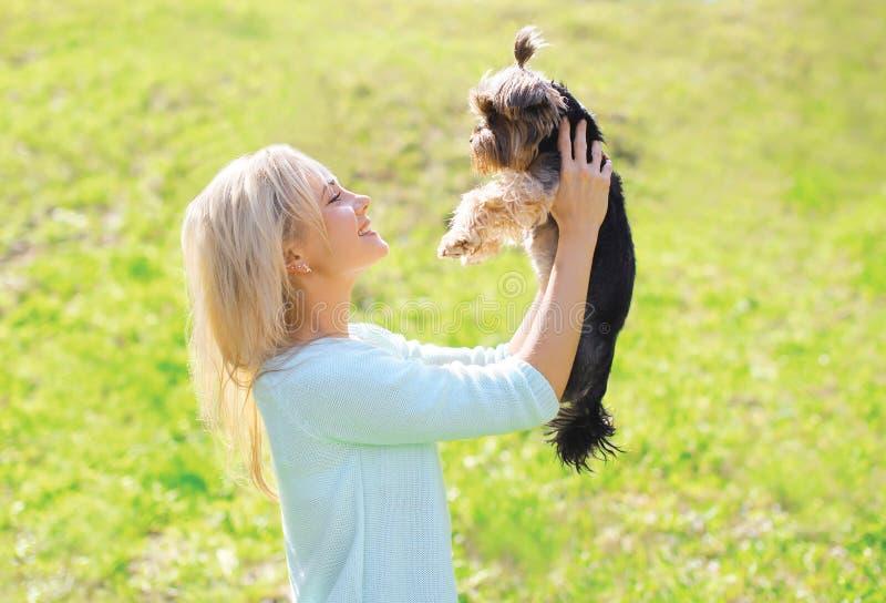 与约克夏狗狗的愉快的少妇所有者 库存图片