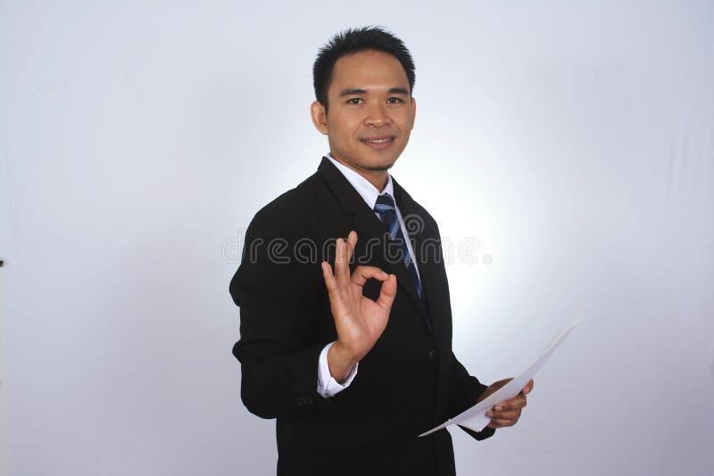 与纸和显示在白色隔绝的好标志的愉快的年轻亚洲商人 免版税库存图片