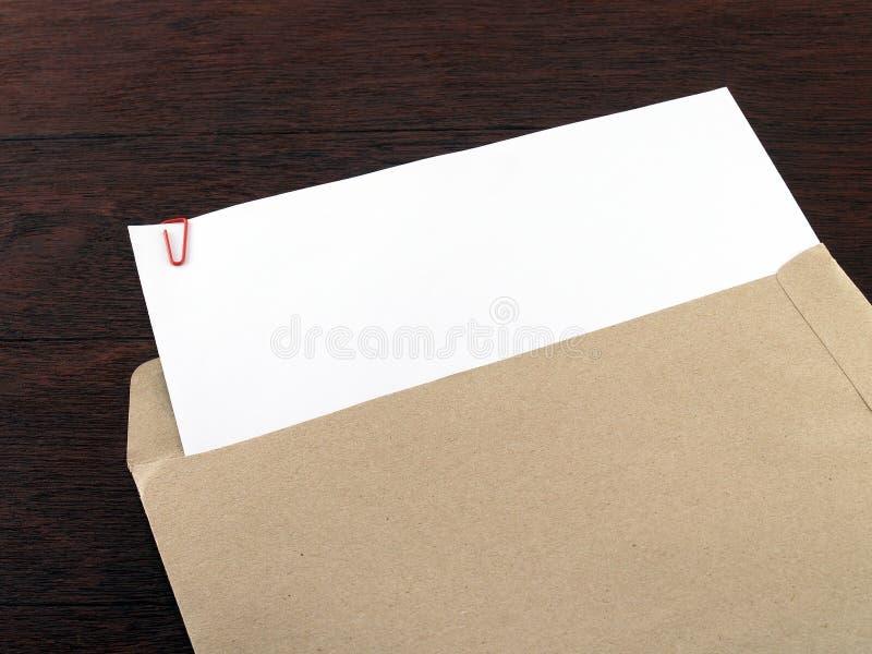 与纸夹的白皮书在黑褐色木书桌地板上的棕色信封 免版税库存照片