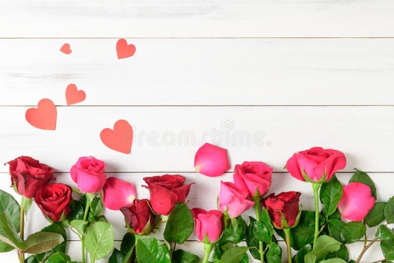与纸心脏的红色和桃红色玫瑰在白色木bcakground 库存图片