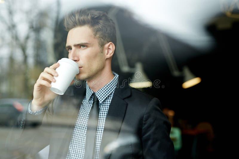 与纸杯的年轻商人 免版税库存照片