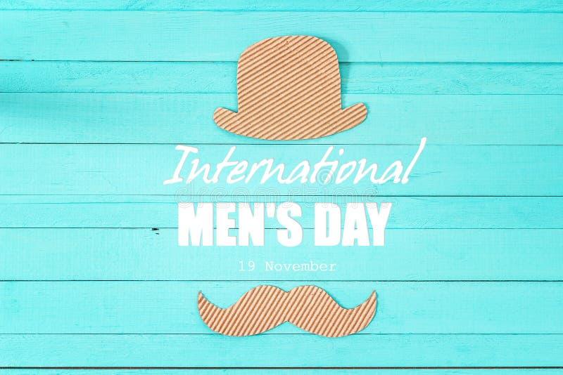 与纸板帽子和mustac的国际人` s天背景 免版税库存图片