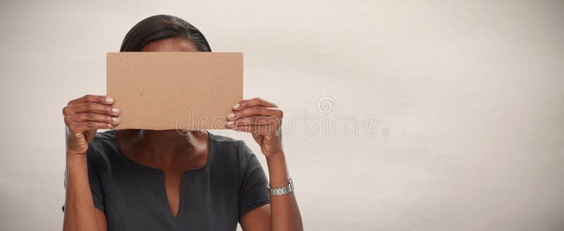 与纸板的女商人掩藏的面孔 库存图片