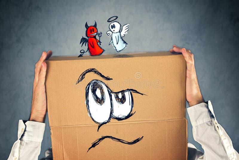 与纸板箱和天使的他的头的商人和恶魔 库存图片