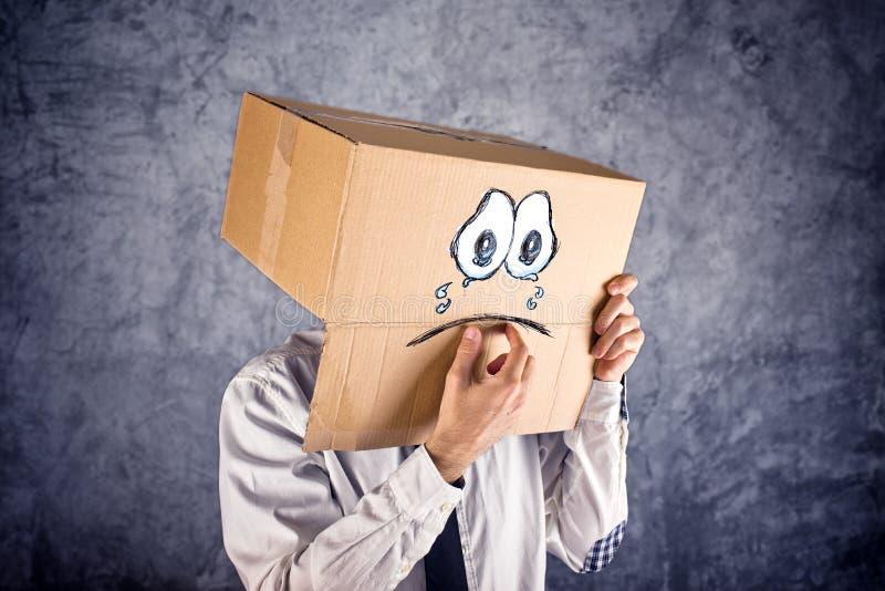 与纸板箱的商人在他的头和哀伤的面孔expressi 免版税库存照片