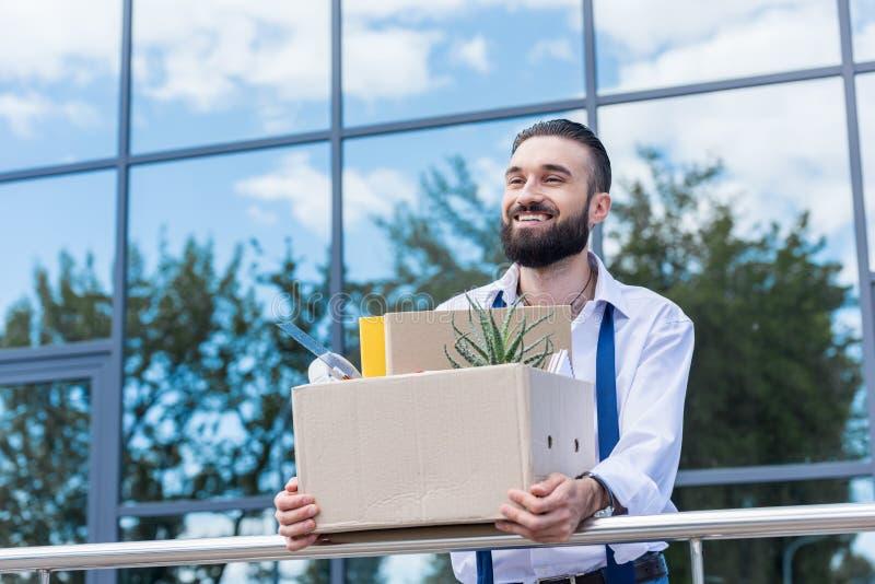 与纸板箱的商人有办公用品的在站立外部办公楼的手上,放弃工作概念 免版税库存图片