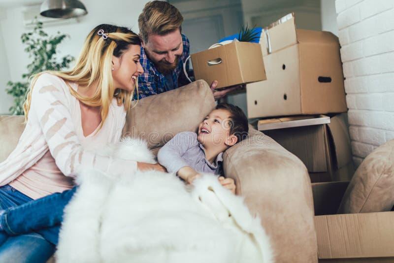 与纸板箱的家庭在新房里移动的天 免版税库存照片