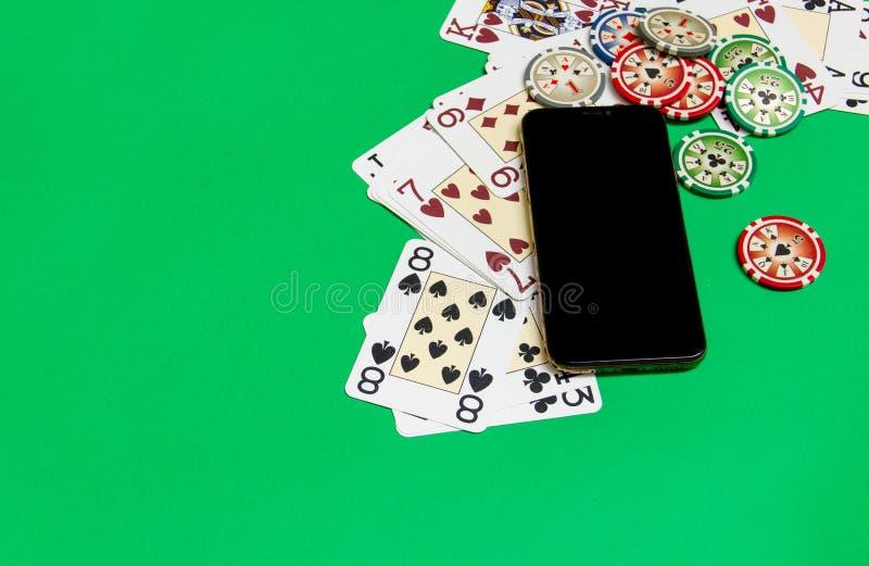 与纸牌的手机和纸牌筹码在一个选材台上 网上赌博娱乐场概念 免版税图库摄影