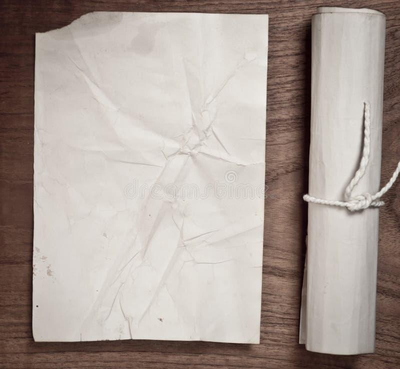 与纸的古老纸卷在木桌上 免版税图库摄影